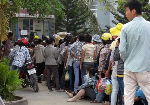 Workers queue up in front of an ATM to withdraw money. — Photo news.zing.vn